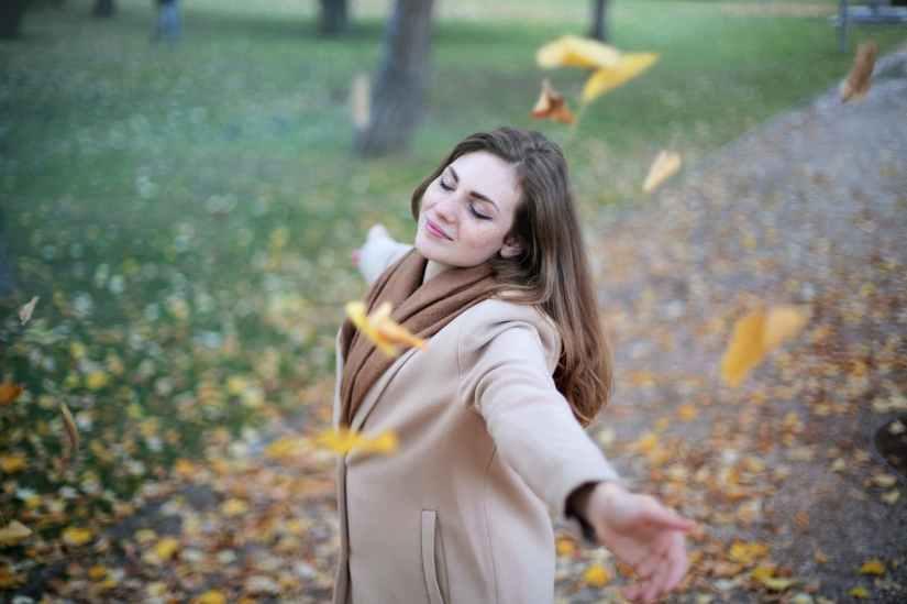Une femme adulte avec les bras écartés respirant l'air dans un jardin en automne.
